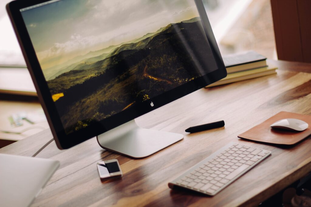 Image of a desktop mac with a green mountain side, alongside a keyboard and apple mouse