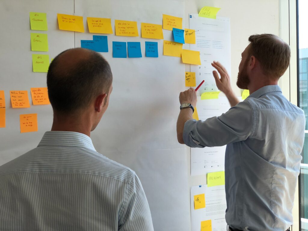 Image showing two men looking at a wall with many post it notes on it, symbolising the similarities when discussing the difference between a business analyst and a product owner.