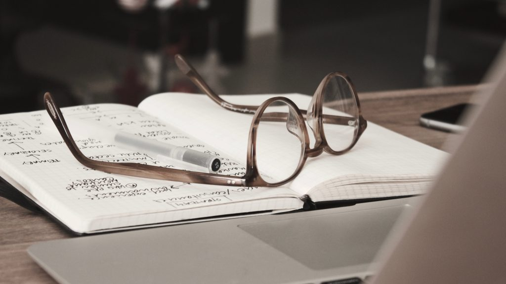 Glasses on top of a notebook to indicate someone thinking about how to combine product management and user research